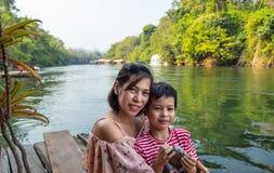 母亲和儿子坐喂养鱼 库存照片