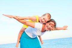 母亲和儿子坐她,愉快使用 免版税库存图片