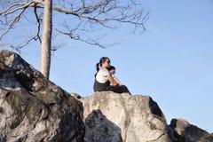 母亲和儿子坐岩石在蓝天背景 图库摄影