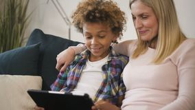 母亲和儿子坐长沙发和观看的滑稽的教育录影在膝上型计算机 股票视频