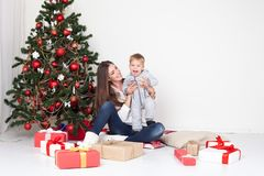 母亲和儿子开放礼物在圣诞节和新年 库存图片