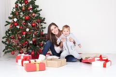 母亲和儿子开放礼物在圣诞节和新年 免版税图库摄影