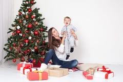 母亲和儿子开放礼物在圣诞节和新年 库存照片