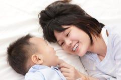 母亲和儿子微笑并且互相查找 免版税库存图片