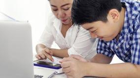 母亲和儿子戏剧和观看的智能手机,移动式摄影车在家被射击与兴高采烈的面孔的愉快的亚洲家庭 影视素材