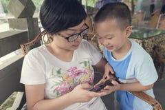 母亲和儿子戏剧智能手机 免版税库存照片