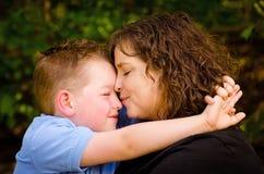 母亲和儿子拥抱与亲吻孩子的妇女 库存图片