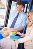 母亲和儿子搭乘公共汽车和使用通行证 免版税图库摄影