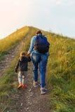 母亲和儿子攀登小山 免版税库存照片