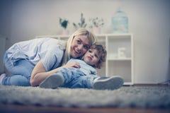 母亲和儿子有一起享用在他们的客厅 图库摄影