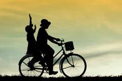 母亲和儿子有乐趣骑马自行车在日落,现出轮廓孩子在日落, 免版税库存照片