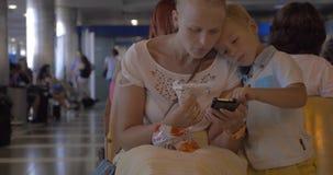 母亲和儿子有手机的在机场休息室 股票视频
