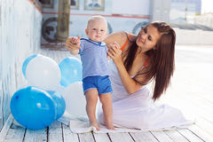 母亲和儿子有蓝色白色气球的 免版税库存图片
