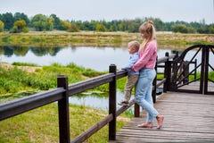 母亲和儿子桥梁的 有站立小的儿子的母亲户外 免版税库存照片