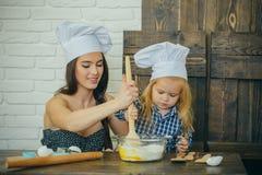 母亲和儿子混合的面粉和鸡蛋在碗 免版税库存照片
