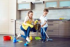 母亲和儿子清洗公寓 免版税库存照片