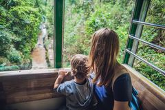 母亲和儿子滑雪电缆车客舱的在夏天在瀑布 P 库存照片