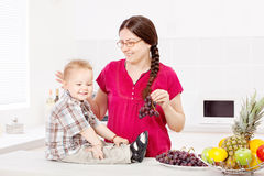 母亲和儿子用果子在厨房里 库存图片
