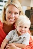 母亲和儿子纵向在家坐沙发 免版税库存图片