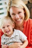 母亲和儿子纵向在家坐沙发 库存图片