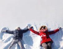母亲和儿子获得一起lounging的乐趣在雪 免版税库存图片