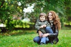 母亲和儿子获得乐趣在公园 免版税图库摄影