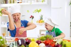 母亲和儿子获得乐趣在厨房食物战争 库存图片