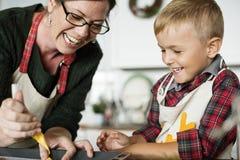 母亲和儿子获得乐趣在厨房 免版税库存照片