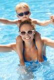 母亲和儿子获得乐趣在游泳池 免版税库存图片