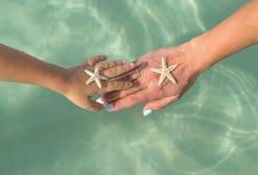 母亲和儿子观看的海星 正面人的情感,感觉,喜悦 做假期和享受夏天的滑稽的逗人喜爱的孩子 免版税库存图片