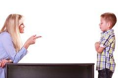 母亲和儿子谈话并且争论坐在桌上 免版税库存照片