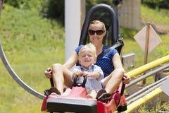 母亲和儿子过山车的乘坐 库存图片