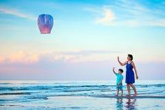年轻母亲和儿子飞行一起射击灯笼 免版税库存照片