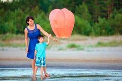年轻母亲和儿子飞行一起射击灯笼 图库摄影
