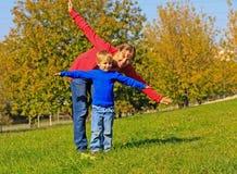 母亲和儿子飞行在秋天公园 免版税库存照片