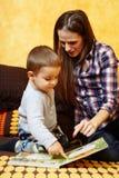 母亲和儿子读书 图库摄影