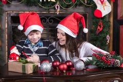 母亲和儿子给圣诞老人的文字信件 免版税库存照片