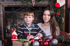 母亲和儿子给圣诞老人的文字信件 免版税库存图片