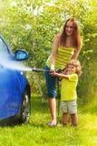 母亲和儿子洗涤汽车 免版税库存照片