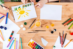 母亲和儿子绘画的手与油漆的在桌上 图库摄影
