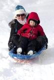 年轻母亲和儿子sledding在雪小山下 免版税库存图片