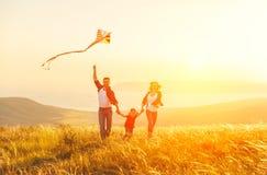 母亲和儿童女儿的愉快的家庭父亲发射风筝o 免版税库存照片