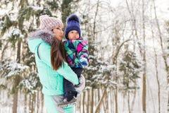 母亲和儿童女孩在一个冬天走本质上 愉快的系列 免版税库存图片