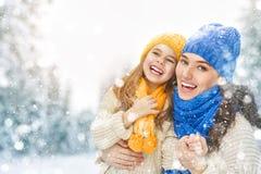 母亲和儿童女孩在一个冬天走 图库摄影