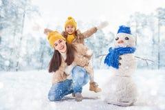 母亲和儿童女孩在一个冬天走 免版税库存照片