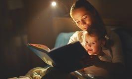 母亲和儿童女孩在床上的读一本书 库存图片