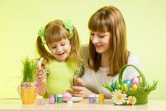 母亲和儿童女孩绘准备对复活节假日的鸡蛋 免版税库存图片