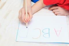 母亲和儿童文字信件的手 免版税图库摄影