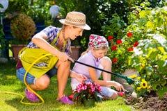 母亲和儿童浇灌的花在庭院里 库存照片