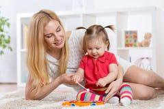 母亲和儿童游戏仪器 库存图片